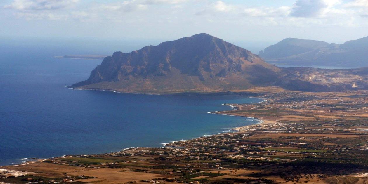 L'immagine mostra un panorama dall'alto del Monte Cofano e della Riserva