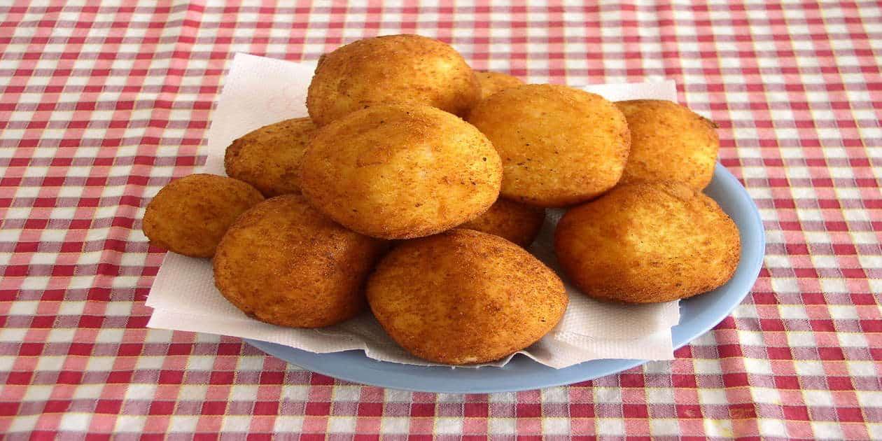 L'immagine mostra un piatto di arancine palermitane